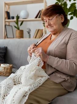 Mulher com foto média fazendo crochê no sofá