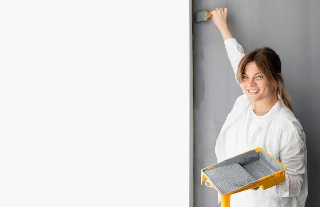 Mulher com foto média pintando parede