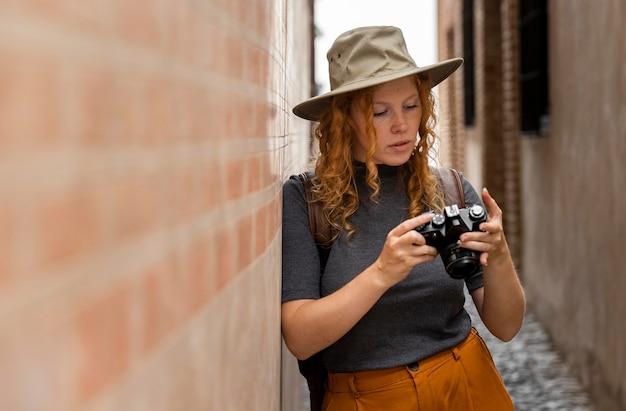 Mulher com foto no meio e chapéu olhando para a câmera