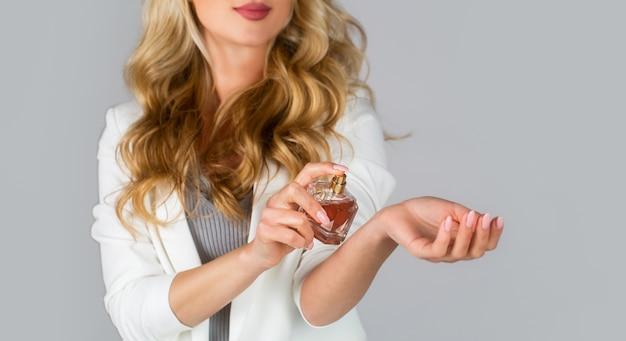 Mulher com frasco de perfume. linda garota usando perfume.