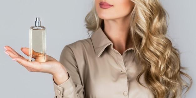 Mulher com frasco de perfume. mulher apresenta fragrância de perfumes.