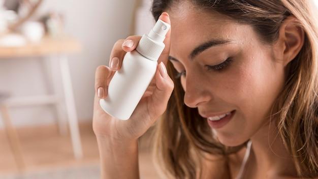 Mulher com frasco de spray