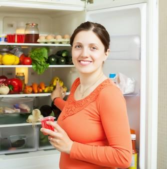 Mulher com frutas perto da geladeira