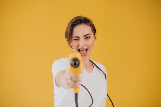 Mulher com furadeira elétrica em fundo amarelo