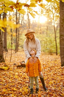 Mulher com garoto na floresta de outono amarela e dourada, mãe e filho caminhando ao ar livre em casacos
