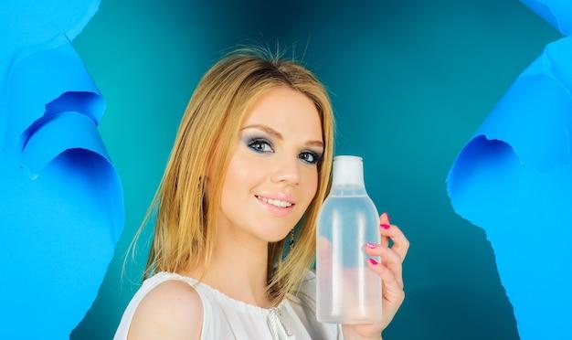 Mulher com garrafa de água micelar. tônico facial. removedor de maquiagem. cuidados com a pele. tratamento de beleza.