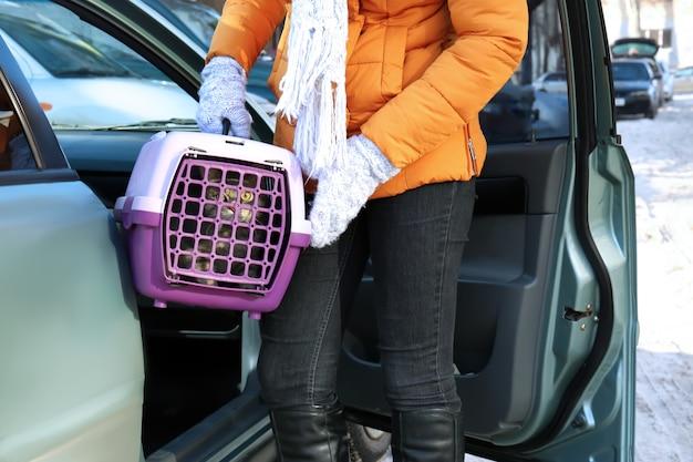 Mulher com gato em caixa de transporte perto do carro