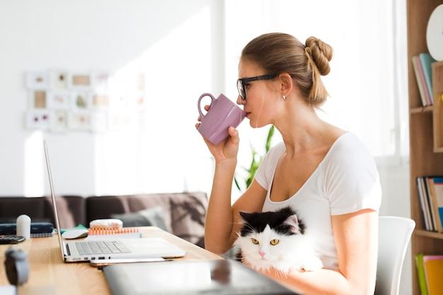 Mulher com gato na mesa trabalhando em casa