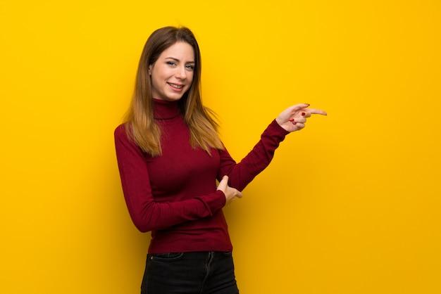 Mulher, com, gola alta, sobre, parede amarela, apontar dedo, ao lado