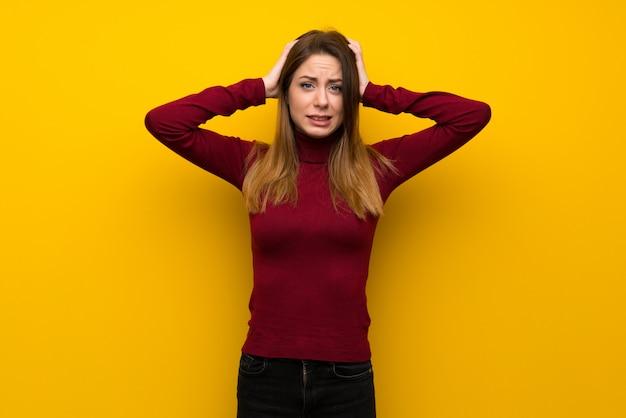 Mulher, com, gola alta, sobre, parede amarela, frustrado, e, leva, mãos cabeça