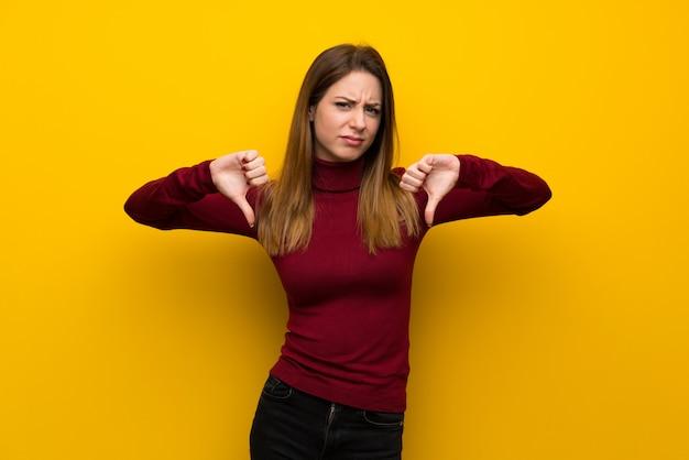 Mulher, com, gola alta, sobre, parede amarela, mostrando, polegar baixo