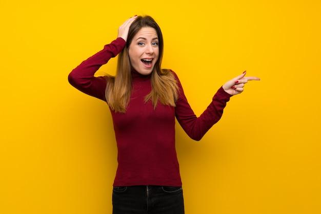 Mulher, com, gola alta, sobre, parede amarela, surpreendido, e, apontar, dedo, ao lado