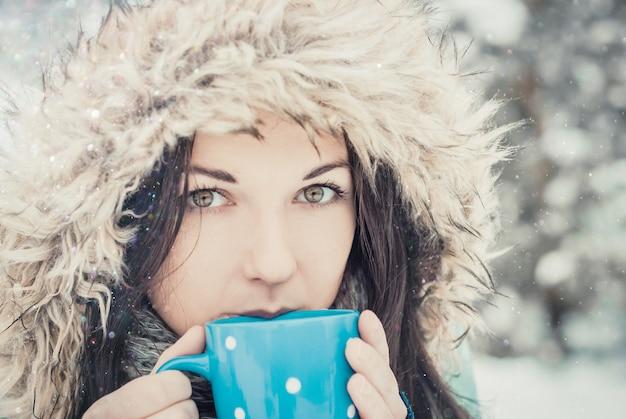 Mulher com grande caneca azul de bebida quente durante o dia frio.
