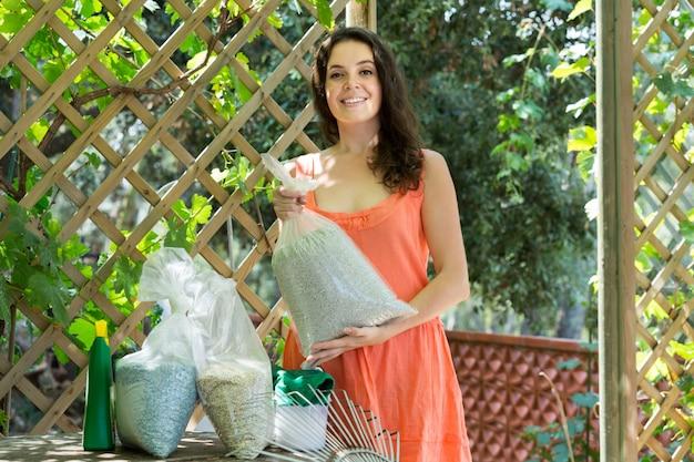 Mulher com grânulos de fertilizantes em saco