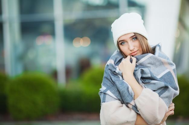 Mulher com gripe ao ar livre, vestindo um cachecol