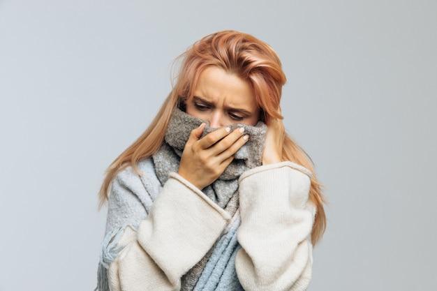 Mulher com gripe envolto em um cachecol quente. rinite, resfriado, alergia