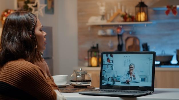 Mulher com gripe usando telemedicina no laptop em casa
