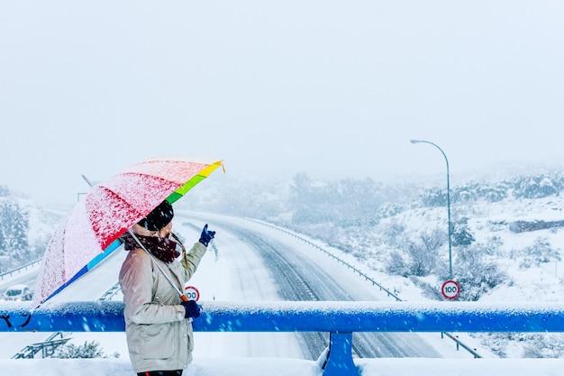 Mulher com guarda-chuva colorido apontando para uma rodovia cheia de neve