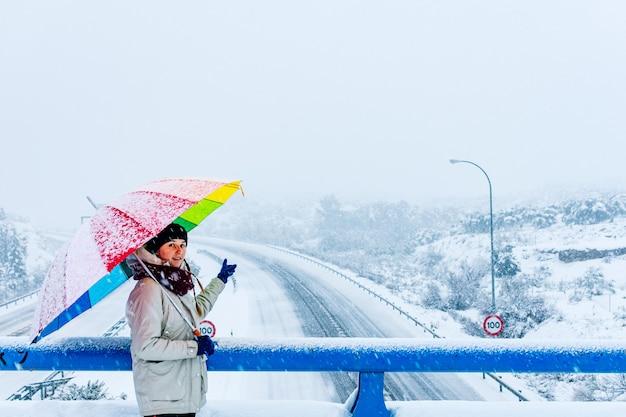 Mulher com guarda-chuva colorido mostrando uma rodovia cheia de neve