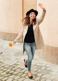 Mulher com guarda-chuva com o braço levantado