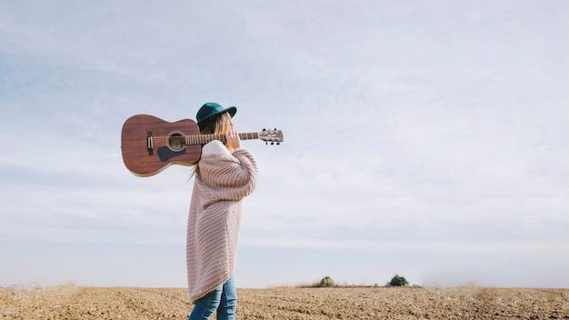 Mulher com guitarra andando no campo