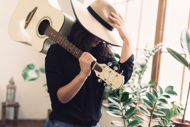 Mulher com guitarra e chapéu de cowboy