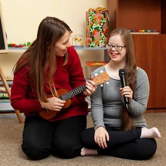 Mulher com guitarra e garota com síndrome de down se divertindo