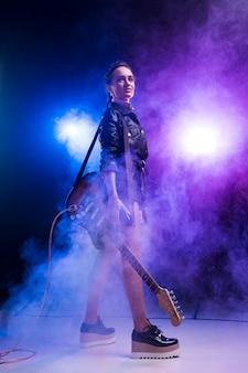Mulher com guitarra elétrica no palco e fumaça