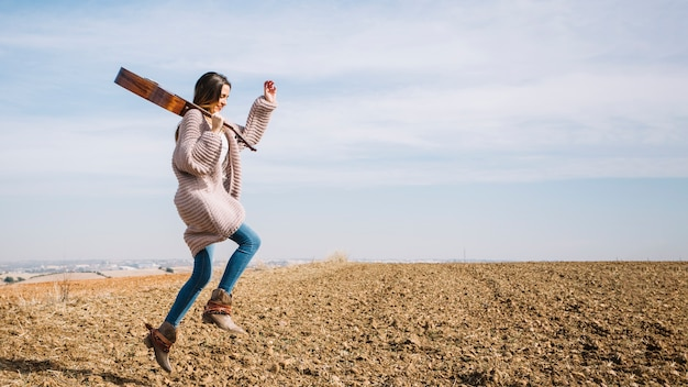 Mulher com guitarra pulando no campo
