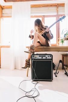 Mulher com guitarra sentada na mesa