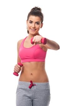 Mulher com halteres durante exercícios intensos