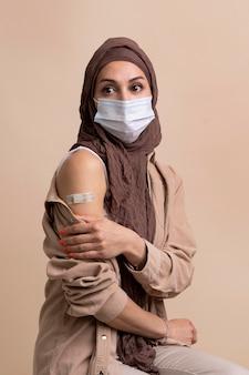 Mulher com hijab mostrando adesivo no braço após tomar vacina