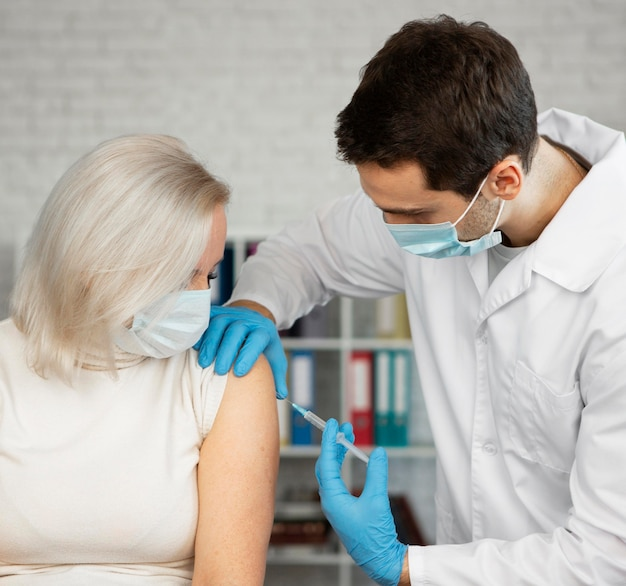 Mulher com injeção média recebendo vacina