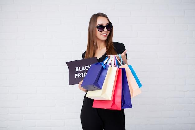 Mulher com inscrição de sexta-feira negra e sacolas de compras