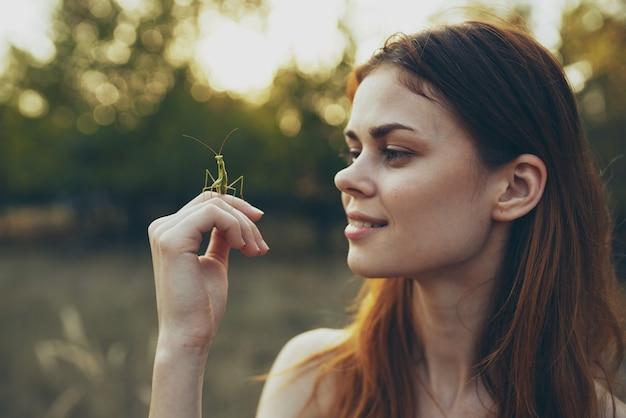 Mulher com inseto na mão rezando árvores natureza louva-a-deus verão