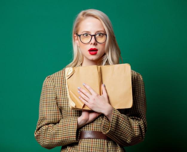 Mulher com jaqueta de estilo britânico com livro na parede verde