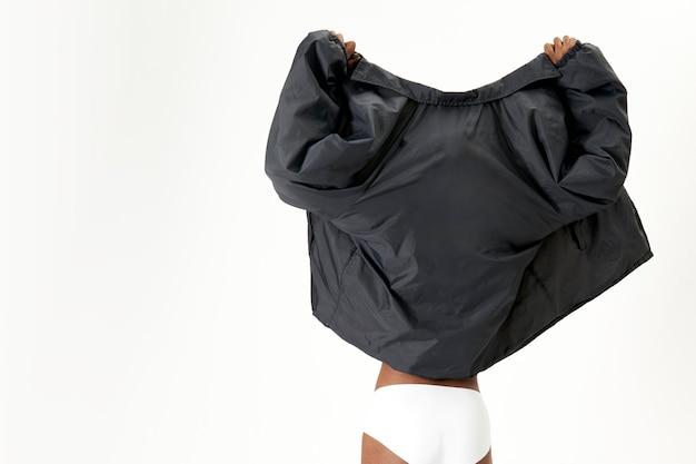 Mulher com jaqueta preta de costas