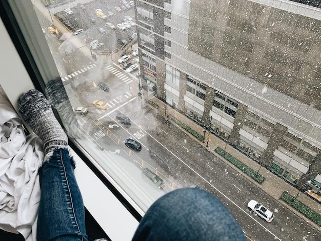 Mulher com jeans e meias perto de uma janela, olhando para as ruas