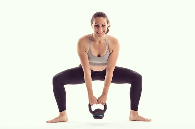 Mulher com kettlebell fazendo exercícios