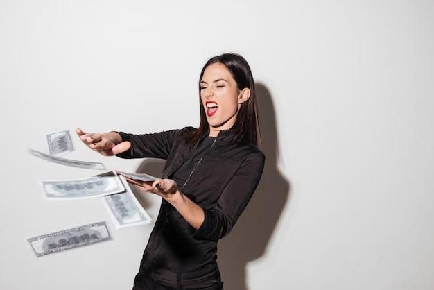 Mulher com lábios vermelhos espalha dinheiro.