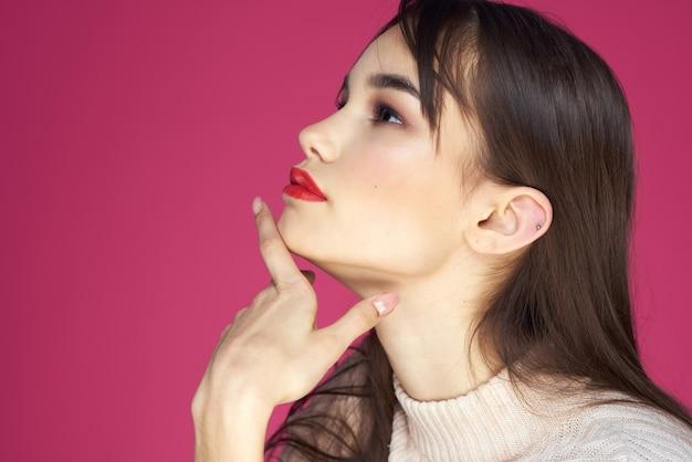 Mulher com lábios vermelhos maquiagem brilhante blusa branca cabelo comprido fundo rosa
