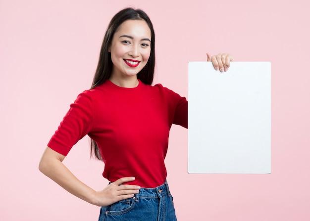 Mulher com lábios vermelhos, segurando a folha de papel em branco