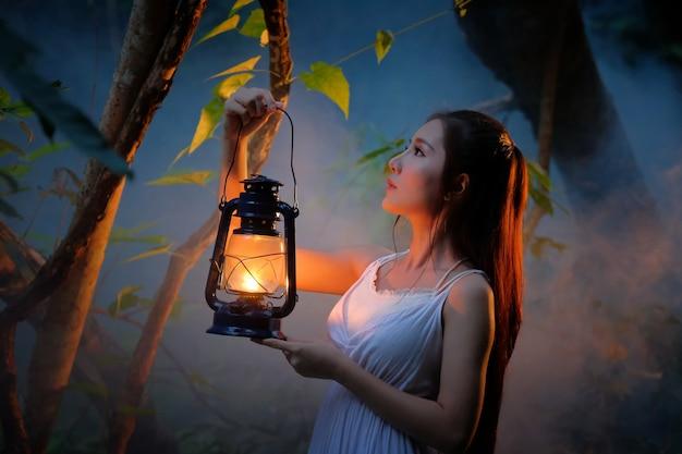 Mulher com lanterna vintage fora à noite