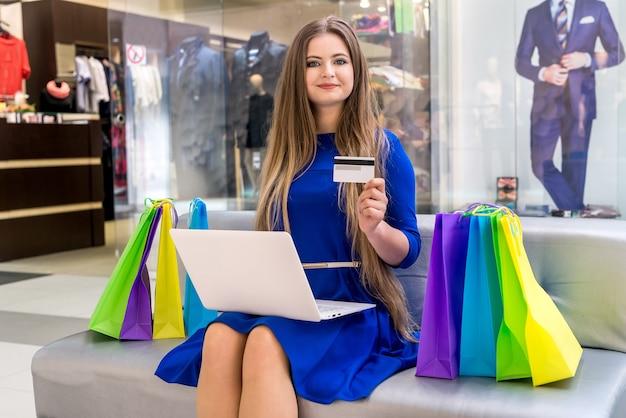 Mulher com laptop e cartão de crédito fazendo compras online