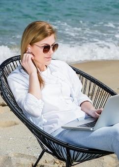 Mulher com laptop e óculos de sol, trabalhando na praia