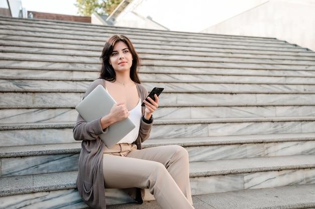 Mulher, com, laptop, e, telefone, cidade