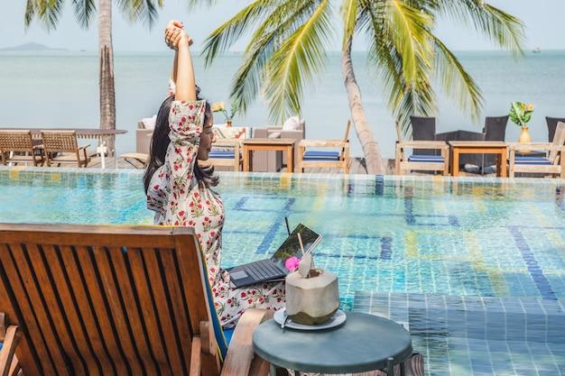 Mulher com laptop esticando os braços acima da cabeça e olhando para a vista do mar