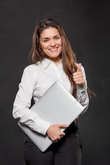 Mulher com laptop mostrando sinal ok