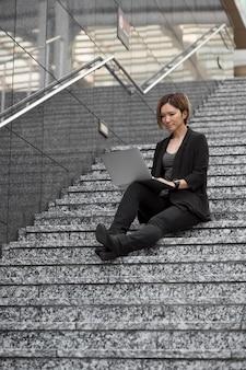 Mulher com laptop na escada