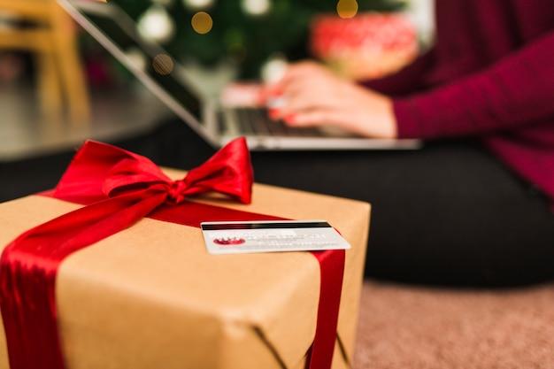 Mulher, com, laptop, perto, cartão crédito, e, caixa presente
